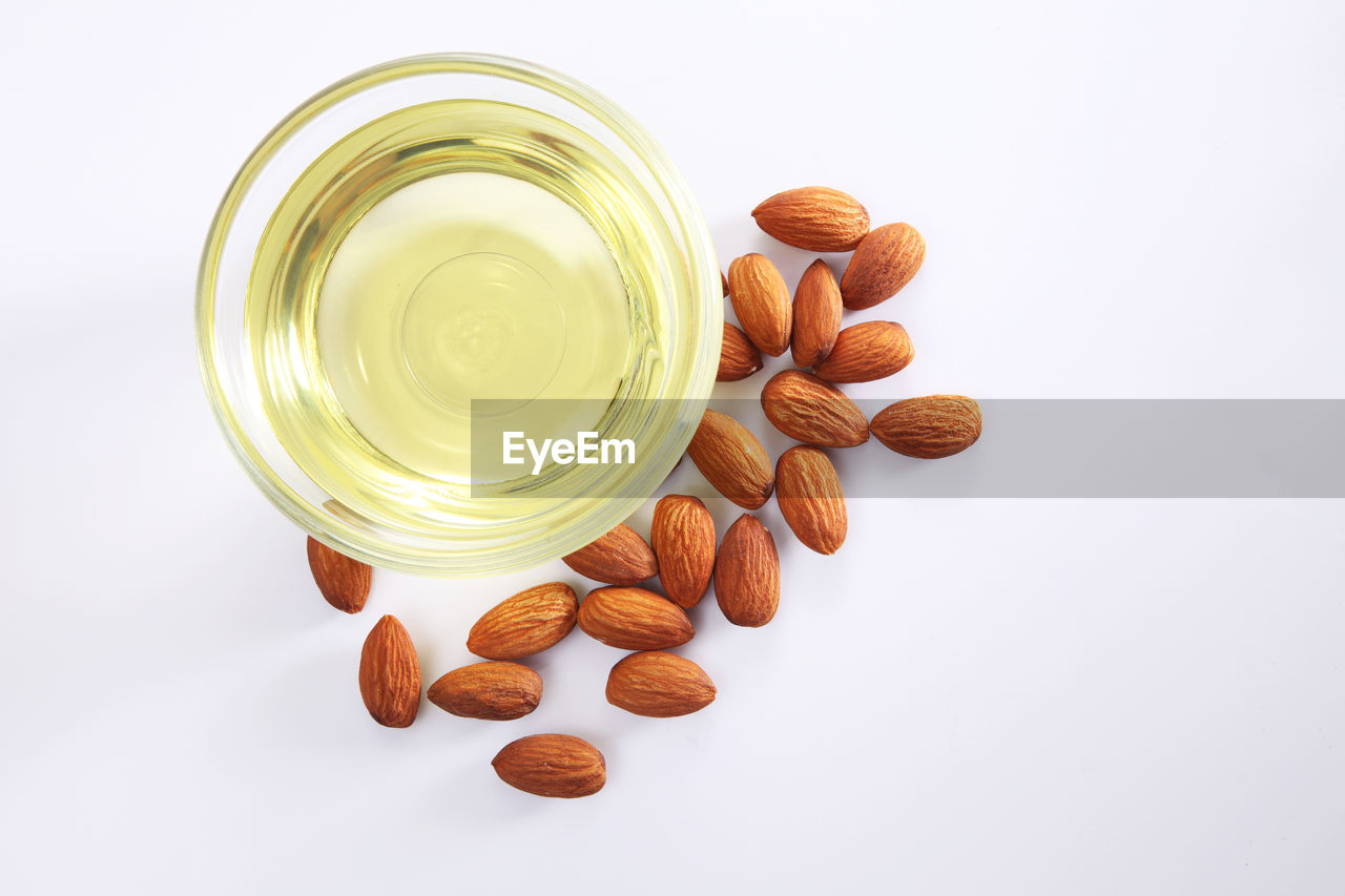 Close-up of cooking oil in bowl and almonds over white background