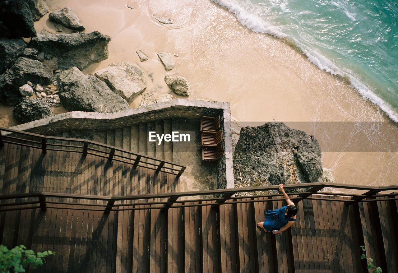 Directly above shot of woman walking on staircase at beach