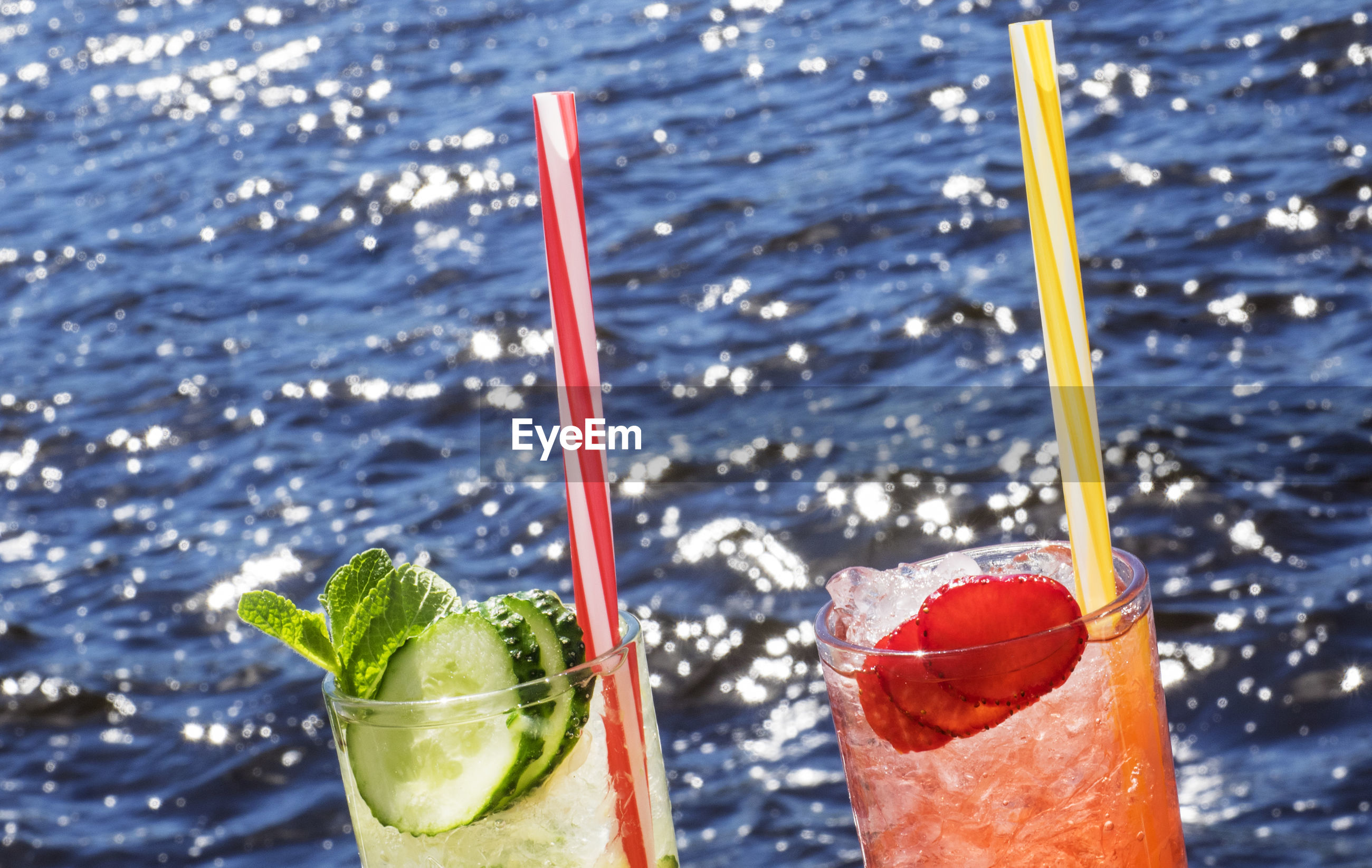 Close-up of drinking glass with alcoholic drink  in sea