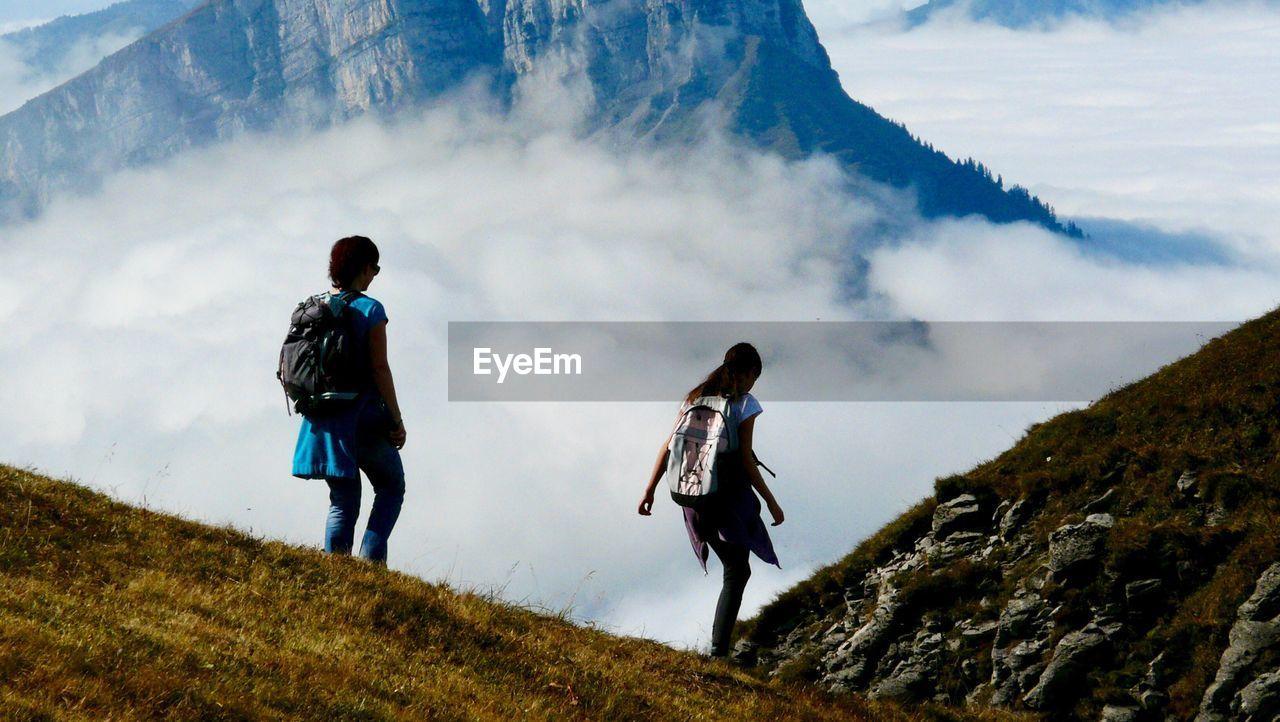 Rear View Of Women Walking On Mountain