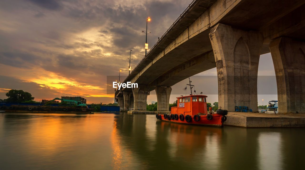 transportation, water, sky, nautical vessel, architecture, built structure, mode of transportation, waterfront, bridge, bridge - man made structure, cloud - sky, river, sunset, connection, reflection, nature, no people, orange color, travel, passenger craft