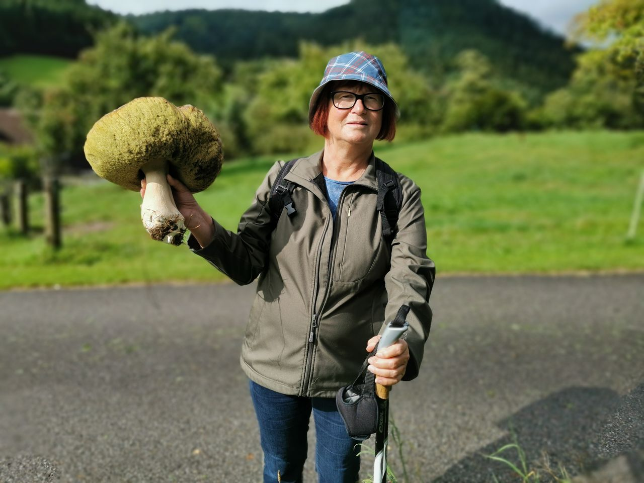one person, real people, holding, three quarter length, day, front view, standing, focus on foreground, leisure activity, nature, field, portrait, lifestyles, casual clothing, plant, looking at camera, road, clothing, outdoors