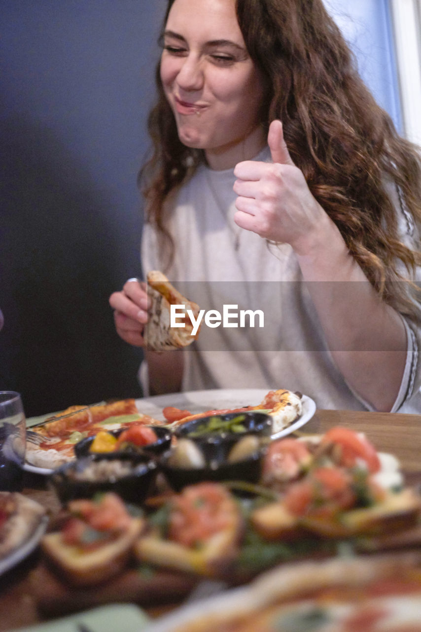 Woman having food at table in restaurant