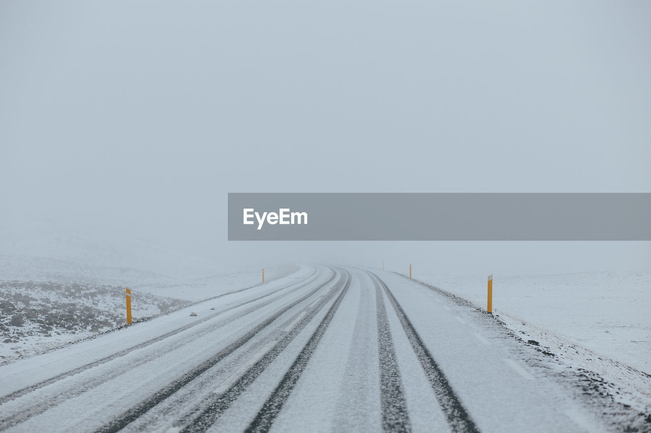 Snow Covered Road Against Sky During Winter