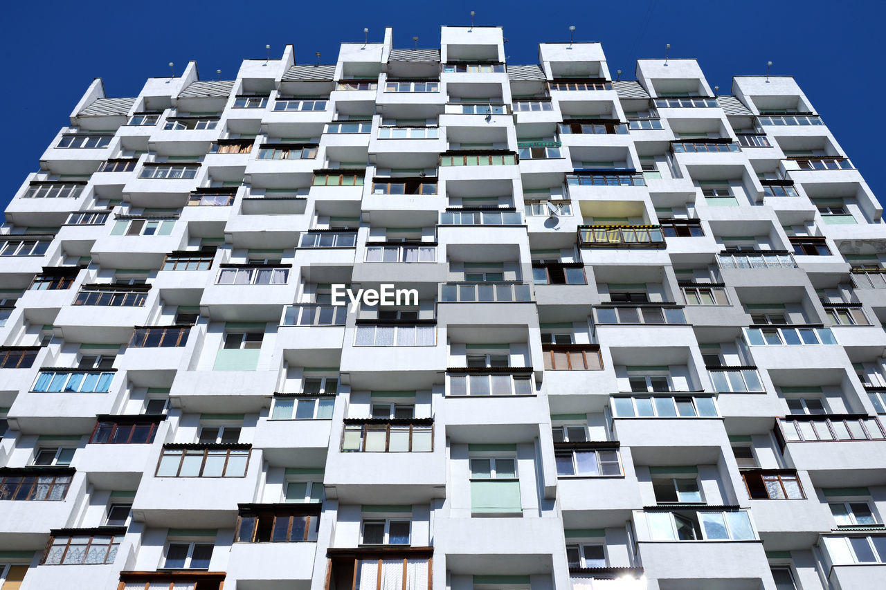 built structure, architecture, building exterior, low angle view, window, no people, balcony, in a row, building, repetition, city, residential district, day, sky, blue, pattern, clear sky, sunlight, outdoors, apartment, office building exterior, skyscraper