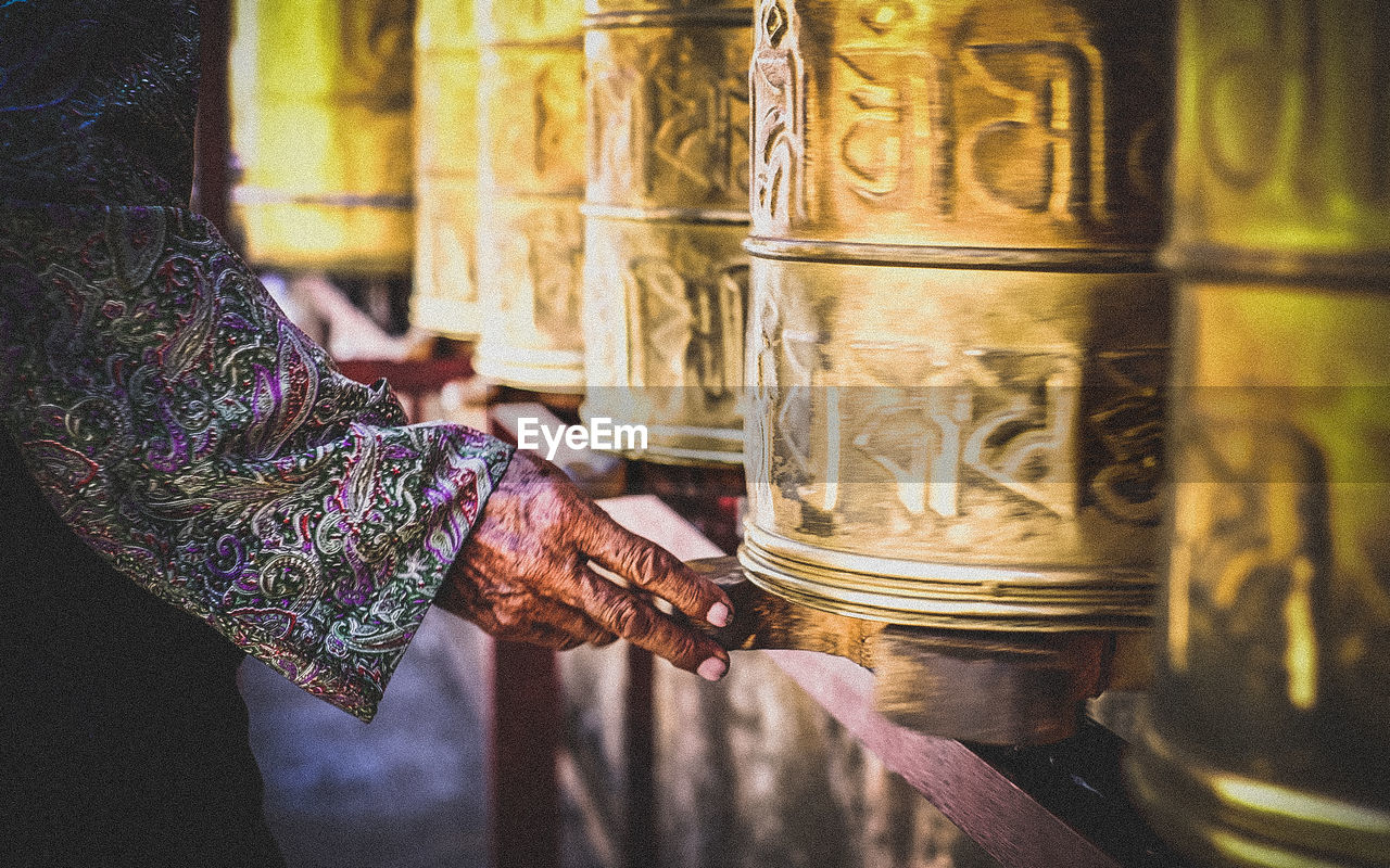 Cropped Hand By Prayer Wheel At Buddha Temple