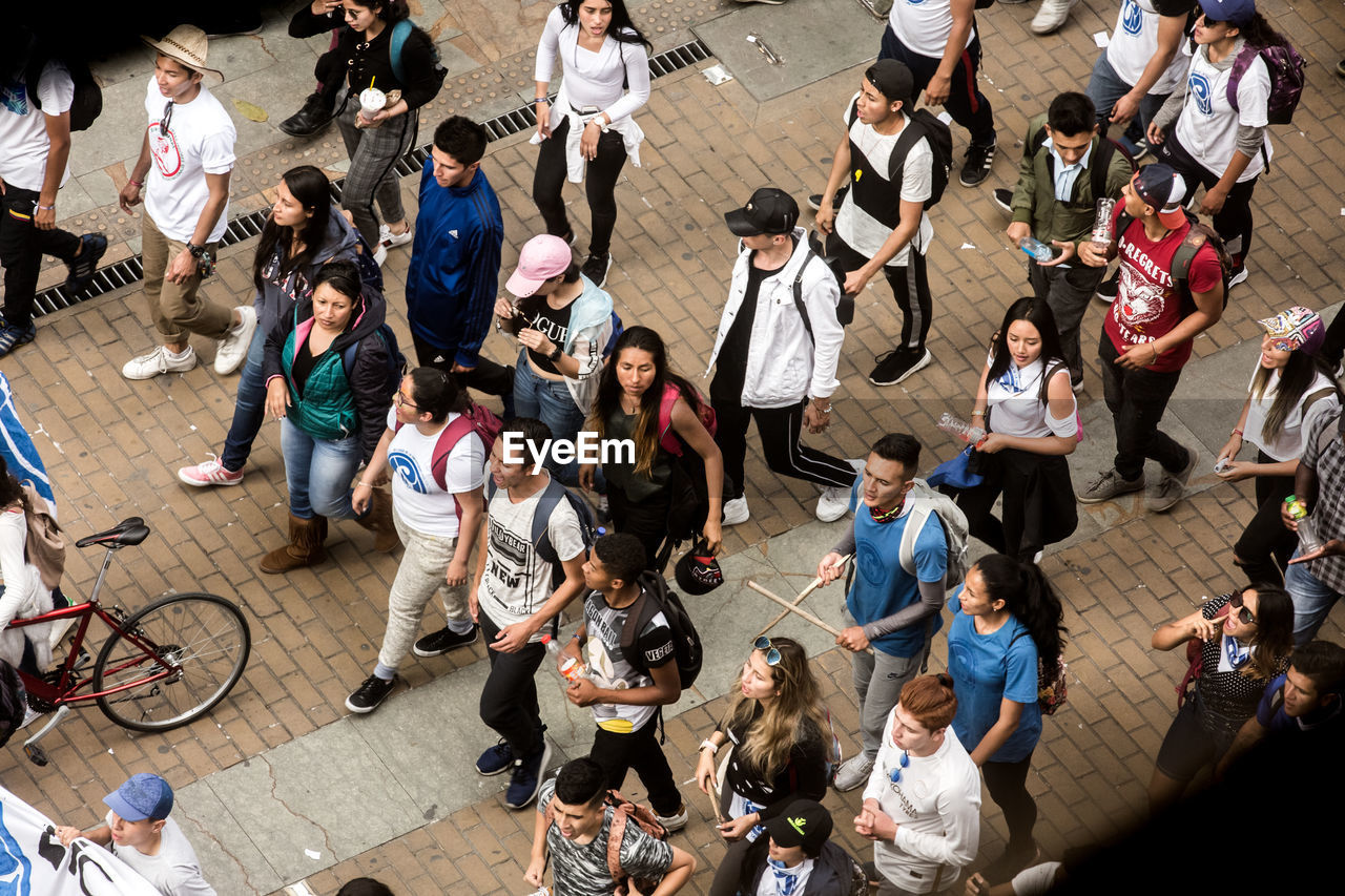 crowd, large group of people, group of people, high angle view, real people, women, men, architecture, adult, lifestyles, standing, city, day, casual clothing, leisure activity, transportation, walking, sitting, outdoors