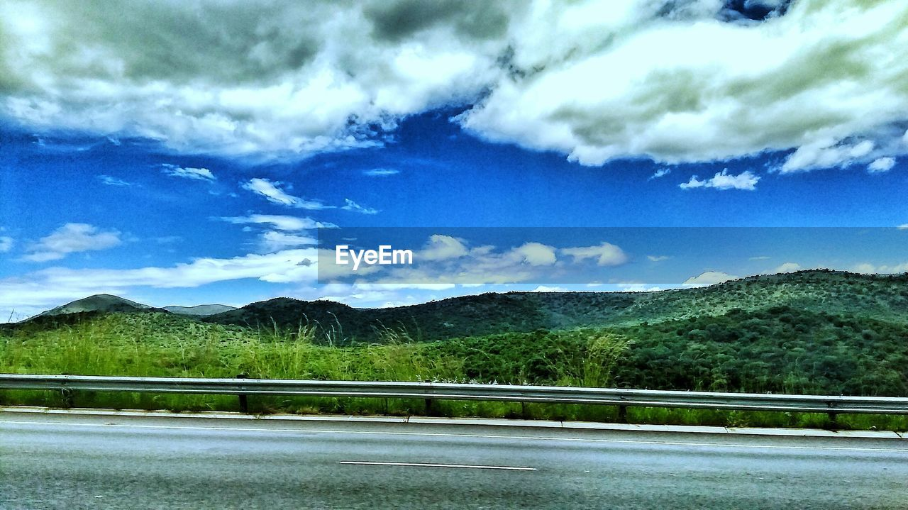 sky, scenics, mountain, nature, road, beauty in nature, tranquil scene, no people, day, tranquility, cloud - sky, outdoors, blue, mountain range, river, transportation, landscape, water