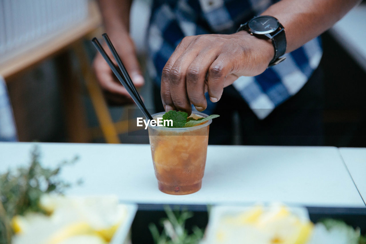 food and drink, hand, human hand, food, real people, one person, freshness, human body part, indoors, table, holding, business, midsection, drink, focus on foreground, refreshment, close-up, men, restaurant, herb, cocktail, glass, finger, mint leaf - culinary, garnish