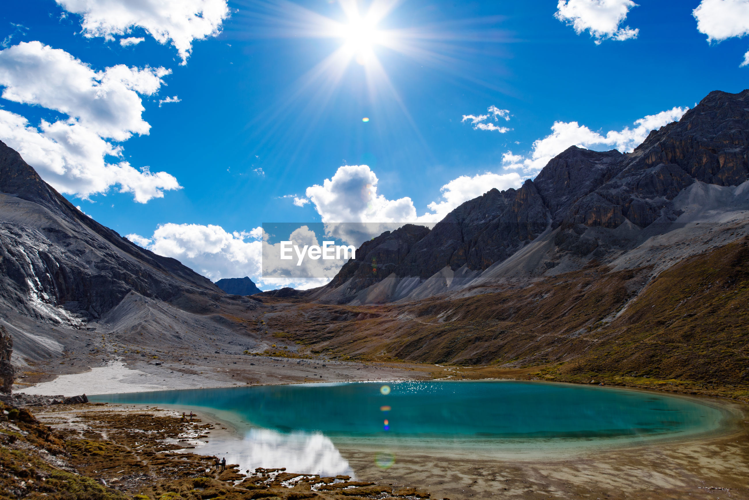 Scenic view of lagoon at mountains against blue sky on sunny day