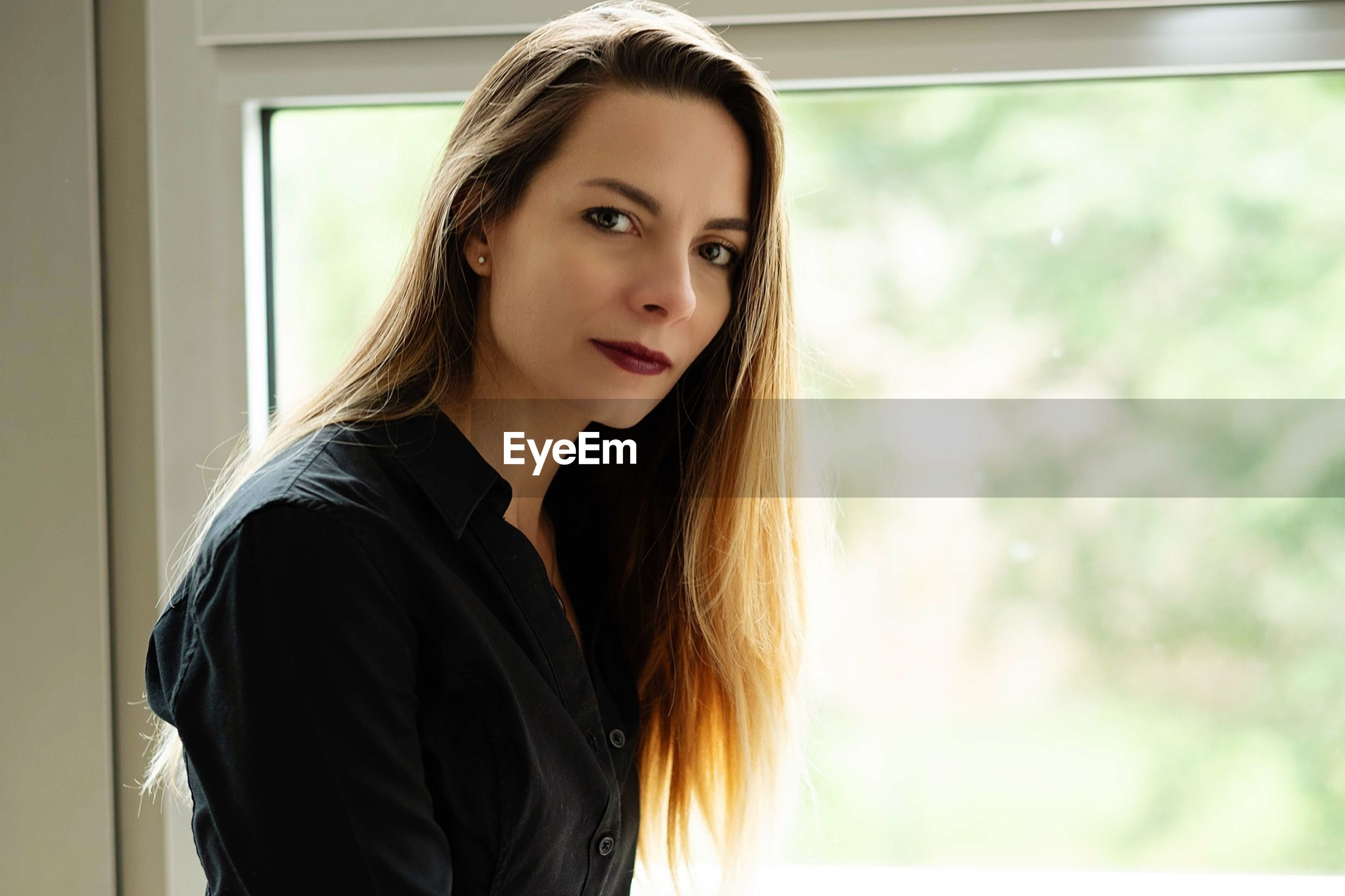 Portrait of beautiful mid adult woman by window at home