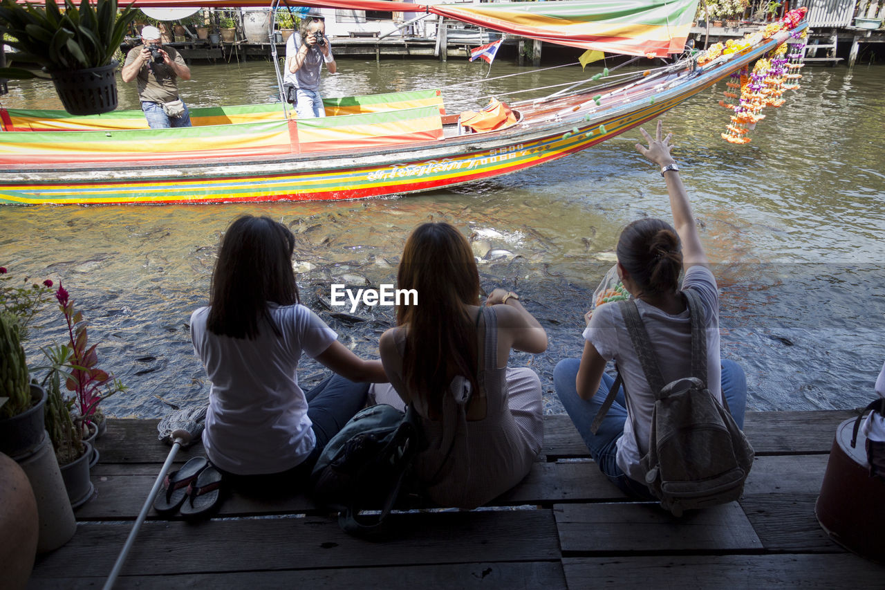 REAR VIEW OF PEOPLE SITTING ON WATER