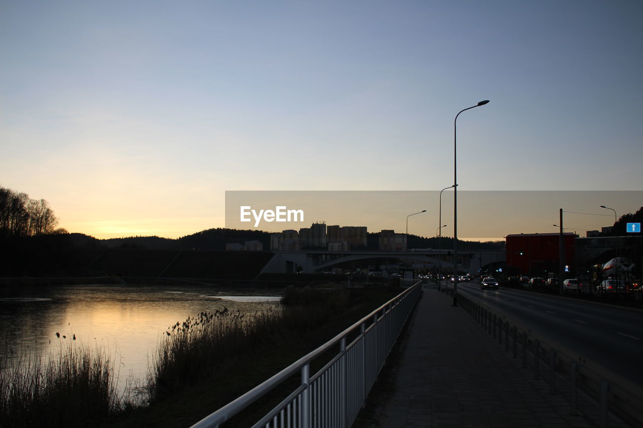 sunset, street light, railing, outdoors, sky, built structure, the way forward, tranquil scene, no people, nature, road, water, scenics, architecture, illuminated, night, beauty in nature