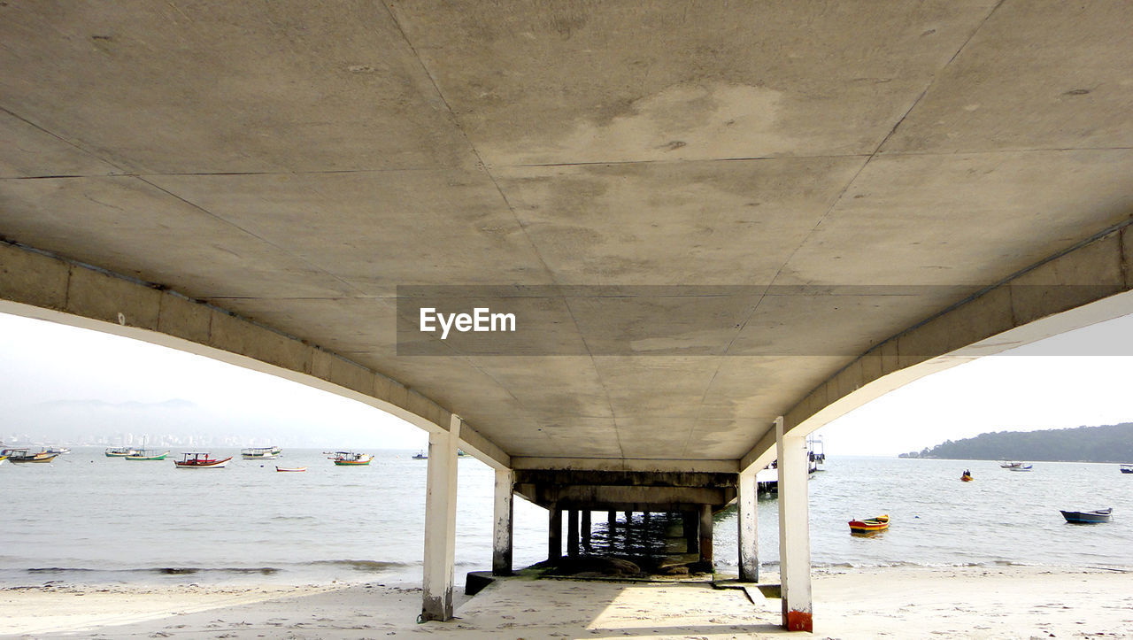 water, architecture, built structure, bridge, sea, beach, connection, bridge - man made structure, day, land, transportation, nature, no people, underneath, below, architectural column, arch, outdoors, sky, ceiling