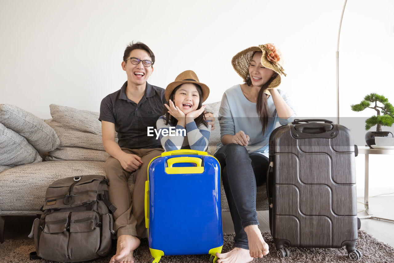 Portrait of family with luggage sitting on sofa