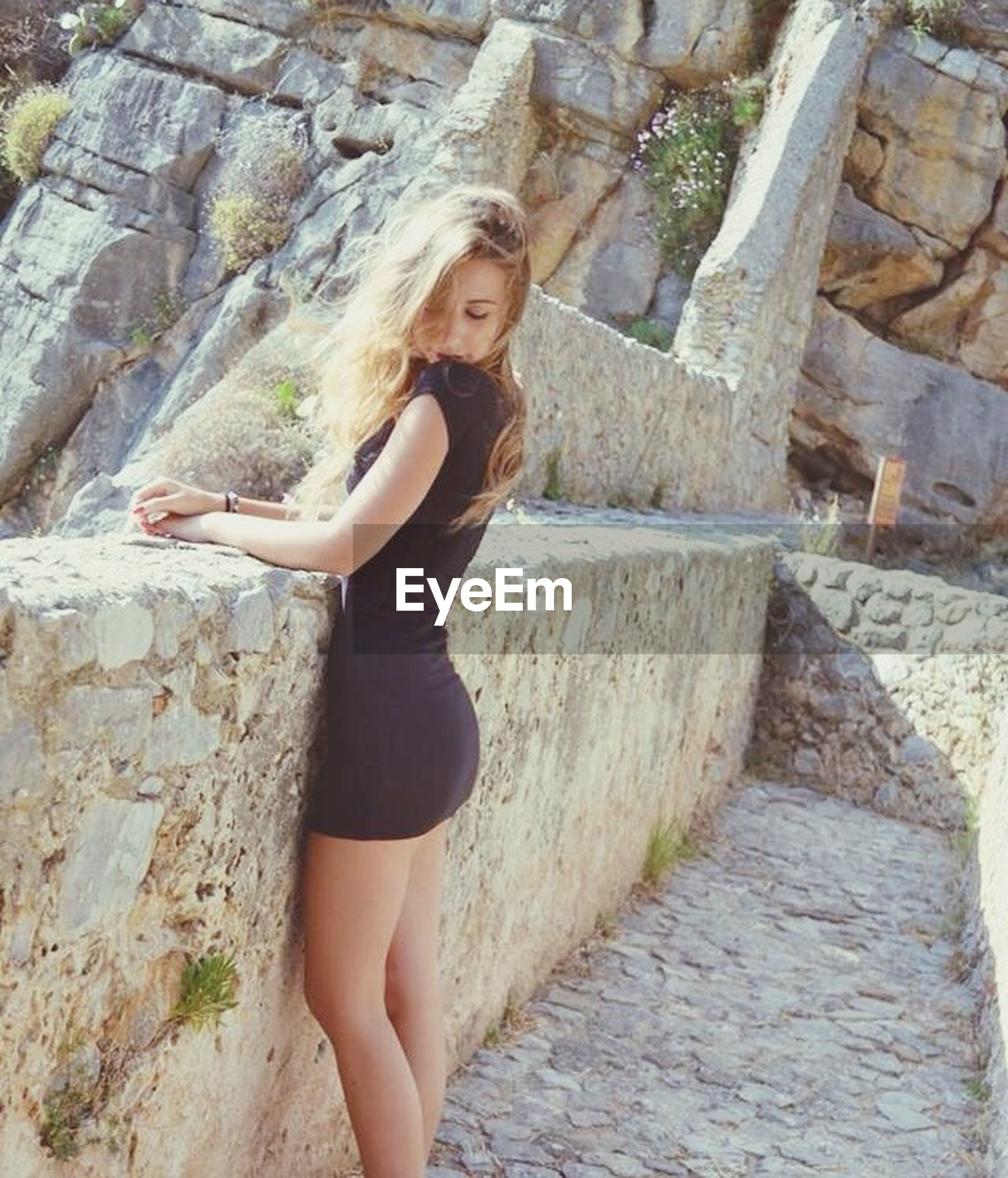 young adult, person, young women, lifestyles, full length, casual clothing, portrait, looking at camera, standing, leisure activity, front view, wall - building feature, stone wall, smiling, sitting, three quarter length
