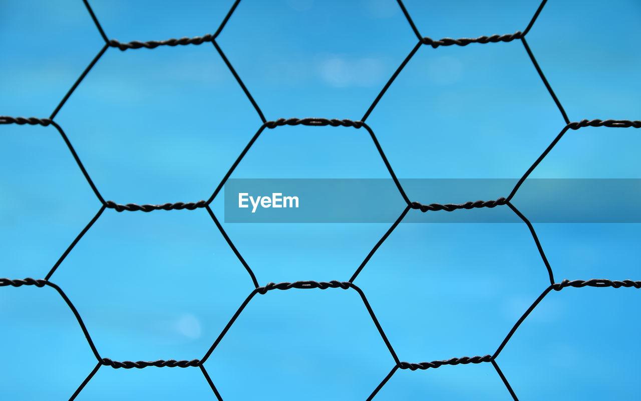 Full Frame Image Of Metallic Fence Against Blue Sky
