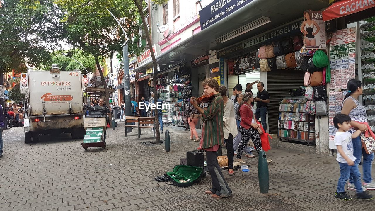 city, street, architecture, real people, group of people, building exterior, built structure, men, adult, people, retail, women, transportation, lifestyles, mode of transportation, land vehicle, city life, shopping, incidental people, day, outdoors, paving stone, retail display