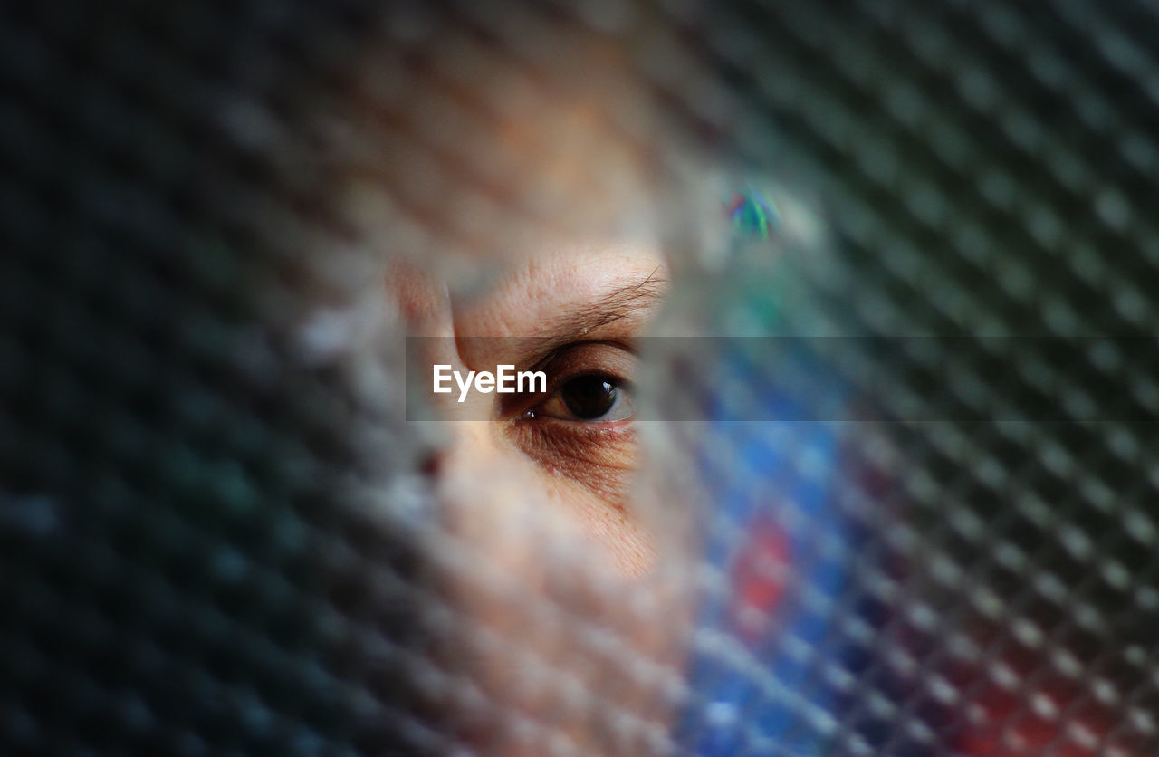 Close-up portrait of woman looking through broken glass