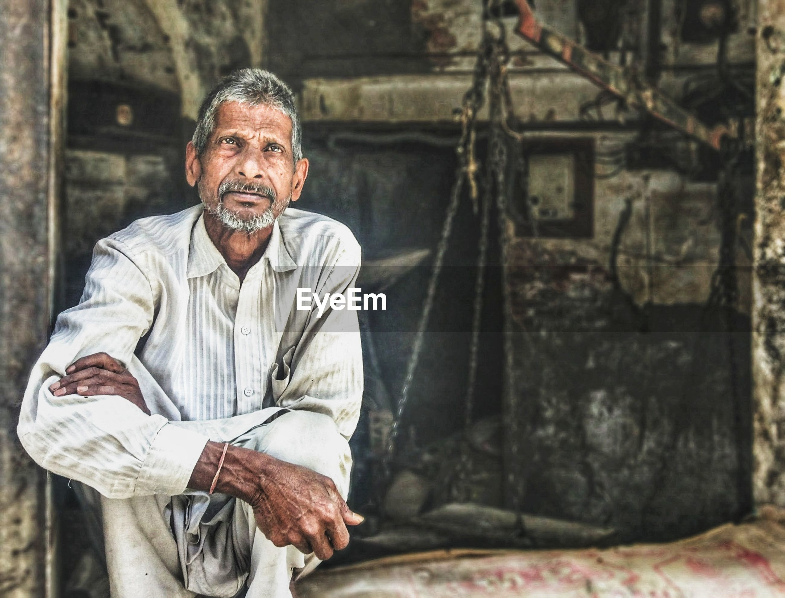 Portrait of mature man sitting at old shop