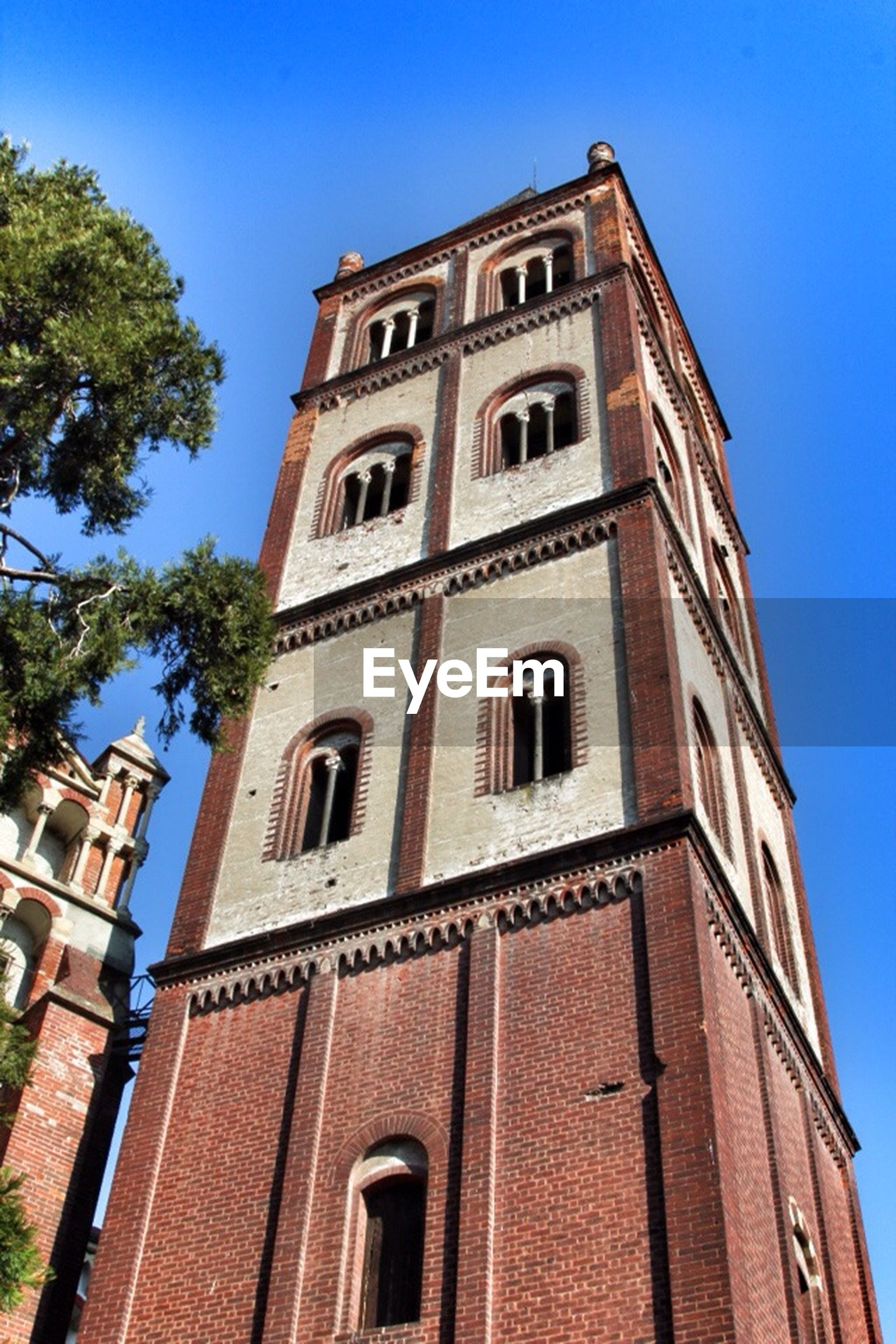 low angle view, architecture, building exterior, built structure, clear sky, blue, window, building, sunlight, day, tree, outdoors, sky, facade, no people, arch, tower, brick wall, city, residential building