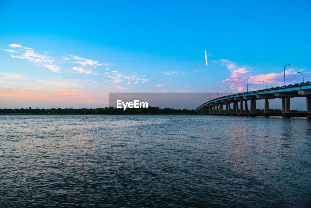 Lake And Bridge Against Blue Sky