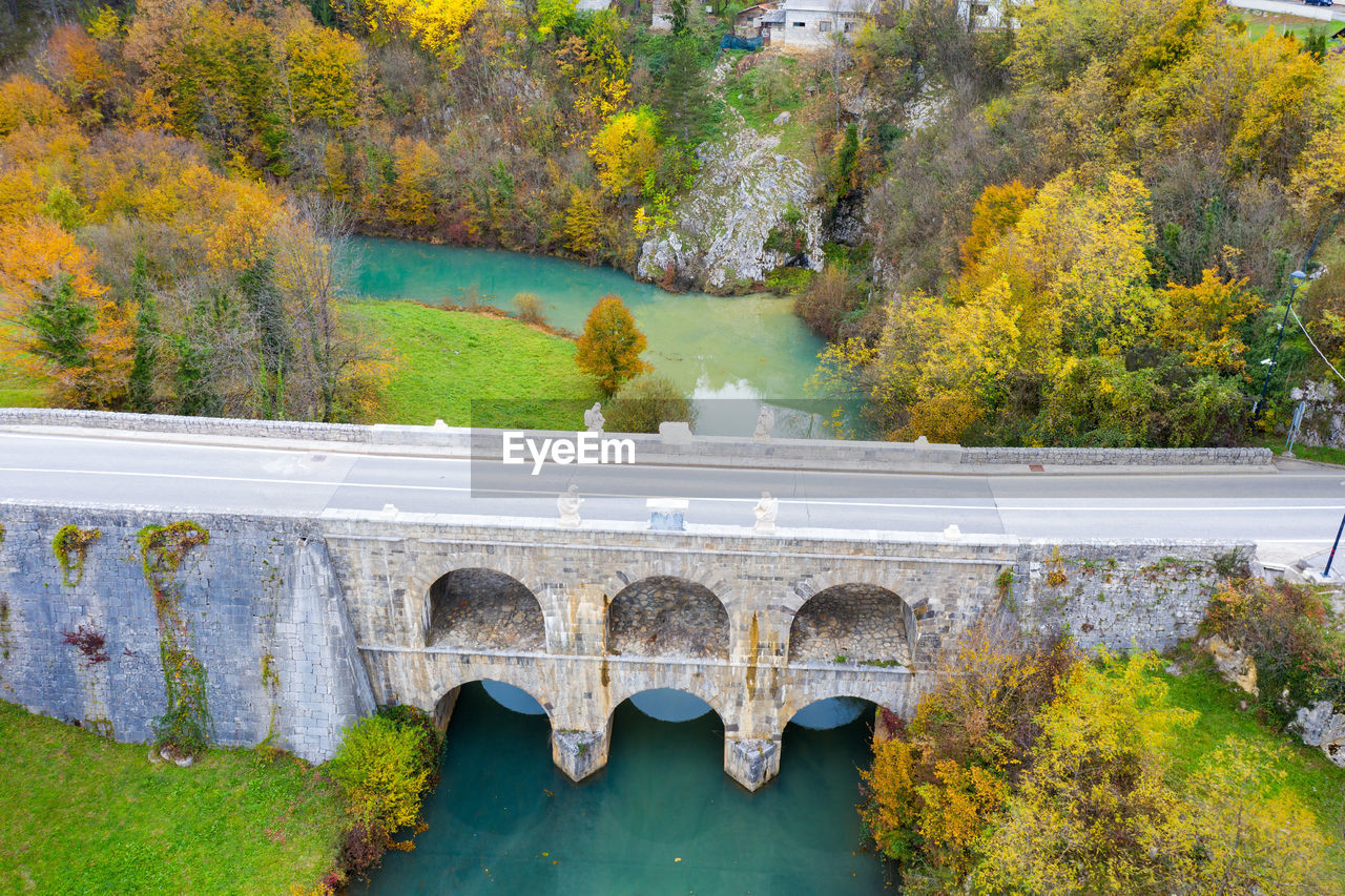 ARCH BRIDGE OVER RIVER BY TREES DURING AUTUMN