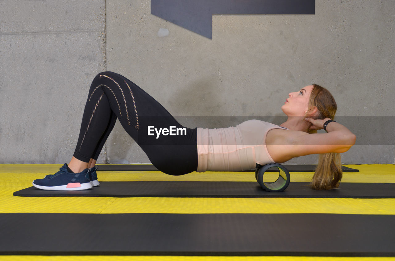 Full Length Side View Of Young Woman Exercising With Foam Roller In Gym