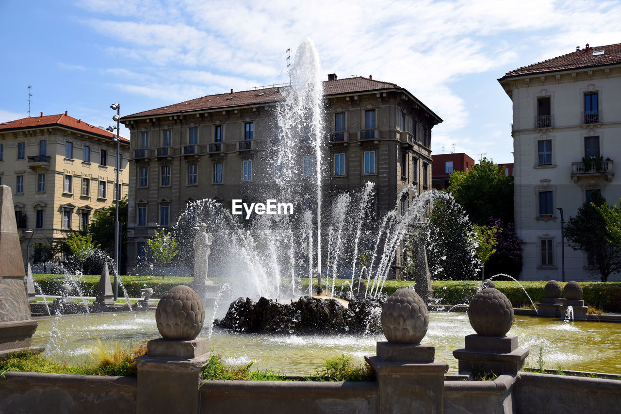 built structure, architecture, fountain, building exterior, water, motion, spraying, nature, splashing, day, sky, cloud - sky, outdoors, building, city, no people, plant, long exposure, flowing water, flowing