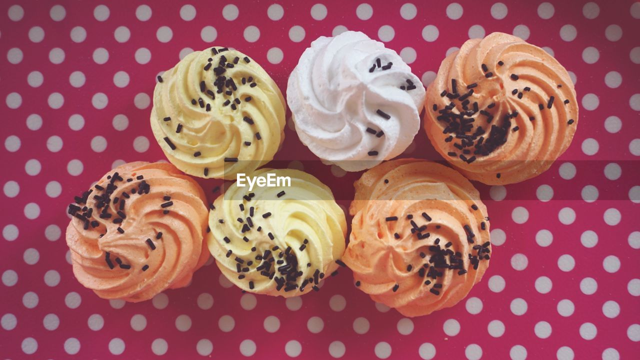 food, food and drink, indoors, sweet food, pattern, no people, freshness, indulgence, sweet, baked, still life, close-up, directly above, choice, variation, group of objects, high angle view, ready-to-eat, dessert, colored background, icing, temptation, polka dot, snack