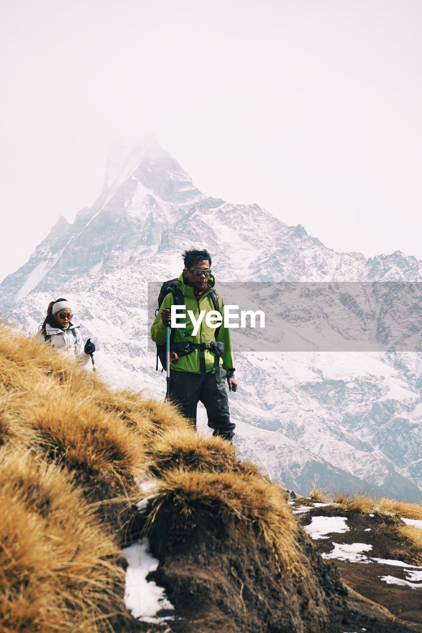 PEOPLE STANDING ON SNOWCAPPED MOUNTAINS AGAINST SKY