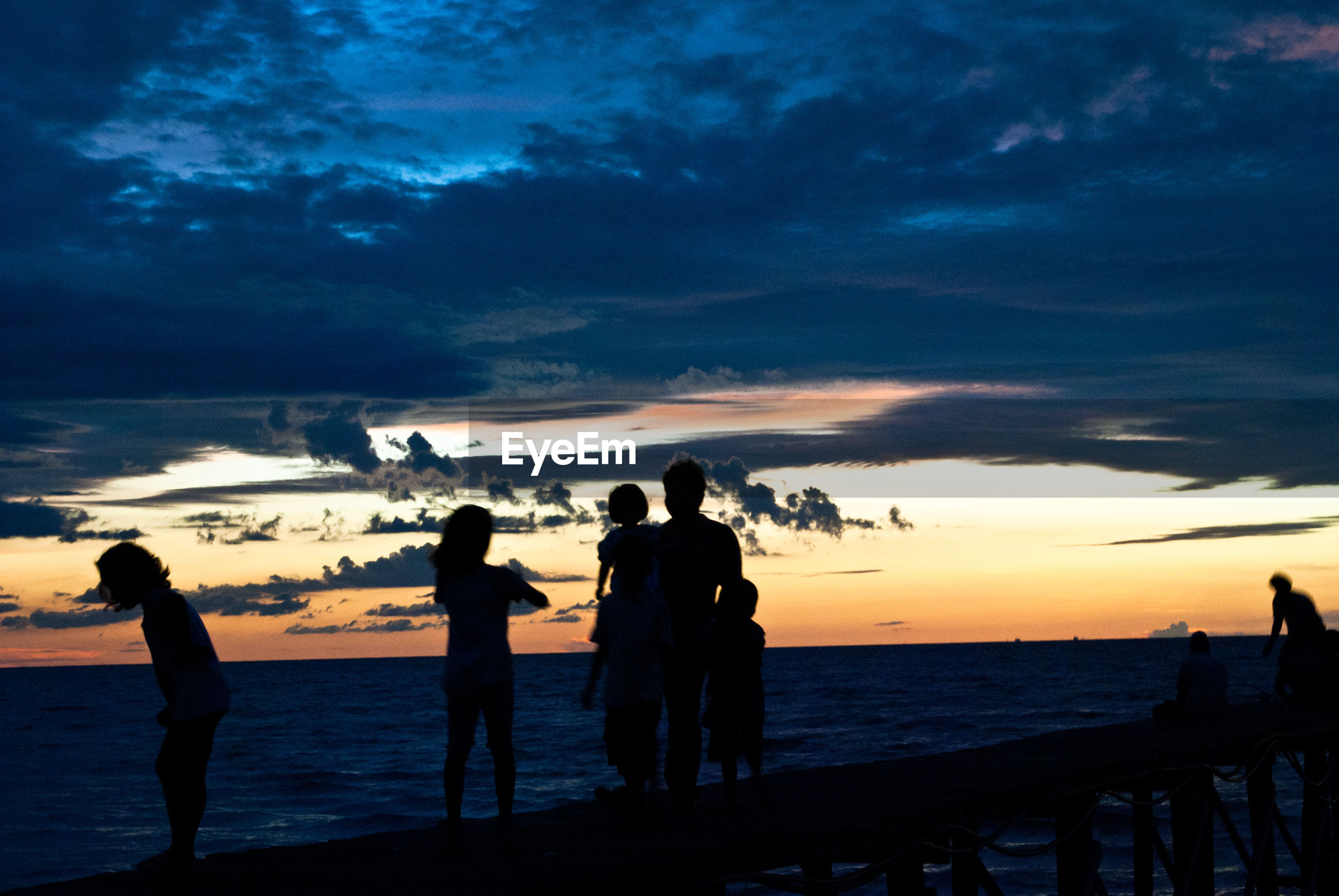 Silhouette people standing on pier over sea against cloudy sky during sunset