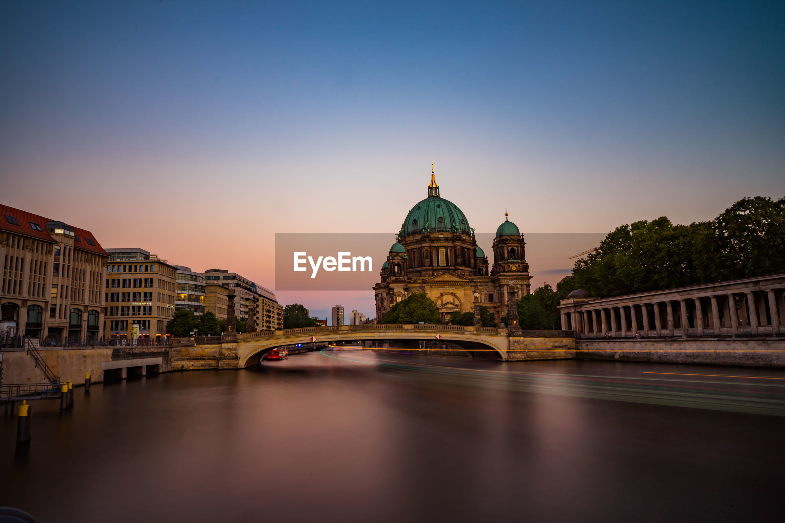 Light trail over river by berlin cathedral against clear sky during sunset