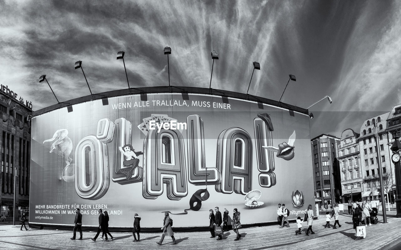 sky, architecture, building exterior, built structure, group of people, city, text, real people, communication, cloud - sky, western script, men, street, women, people, city life, nature, sign, day, outdoors