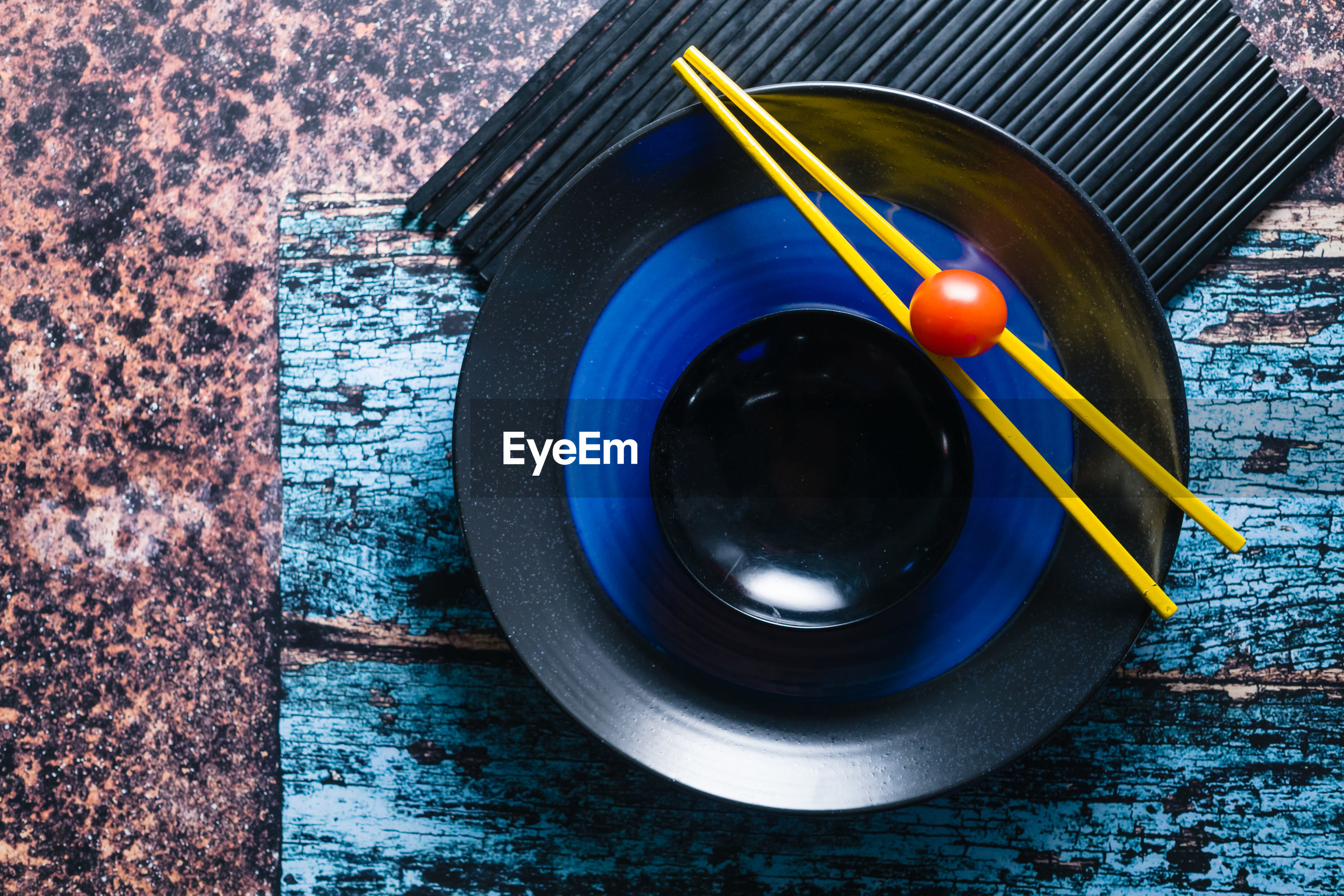 High angle view of small tomato and yellow chopstick in black and blue plate
