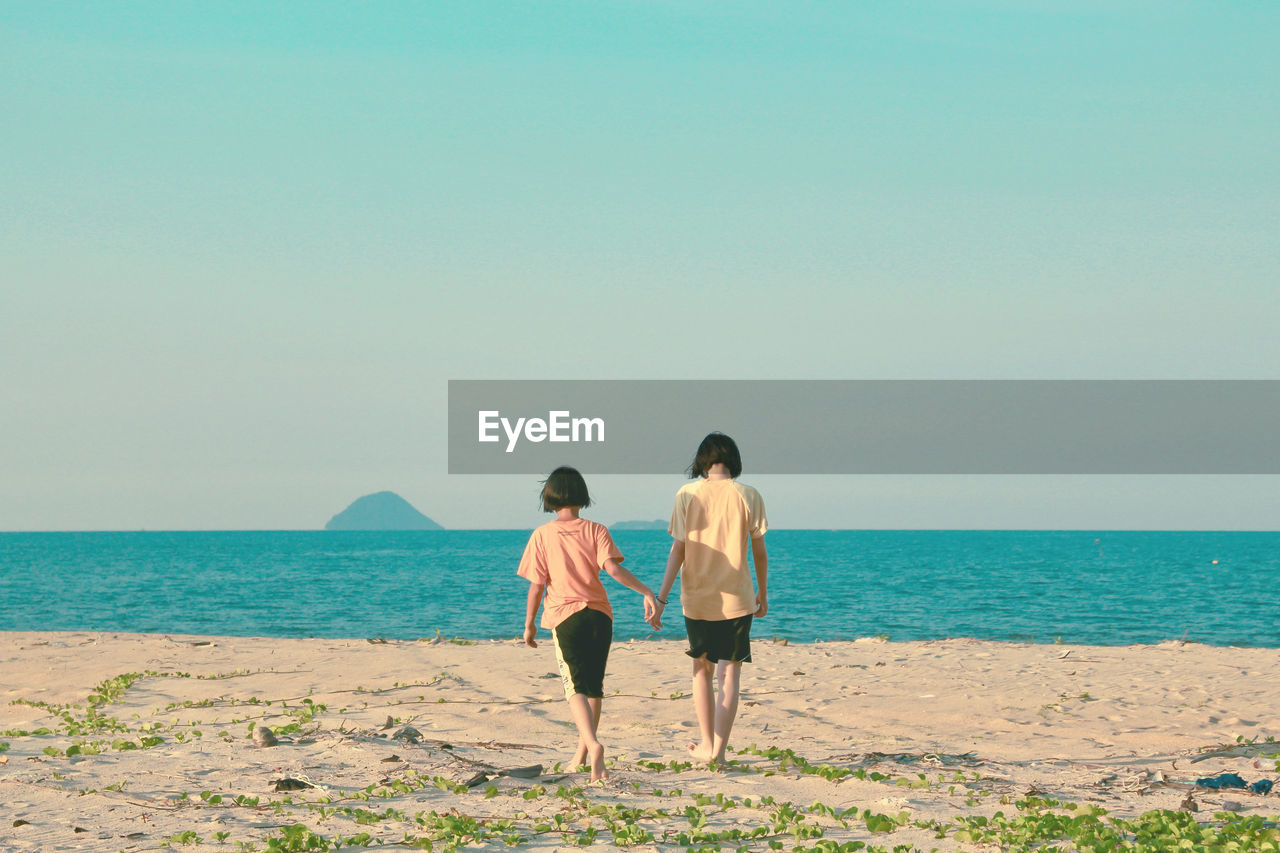 Rear View Of Girls Walking At Beach Against Sky