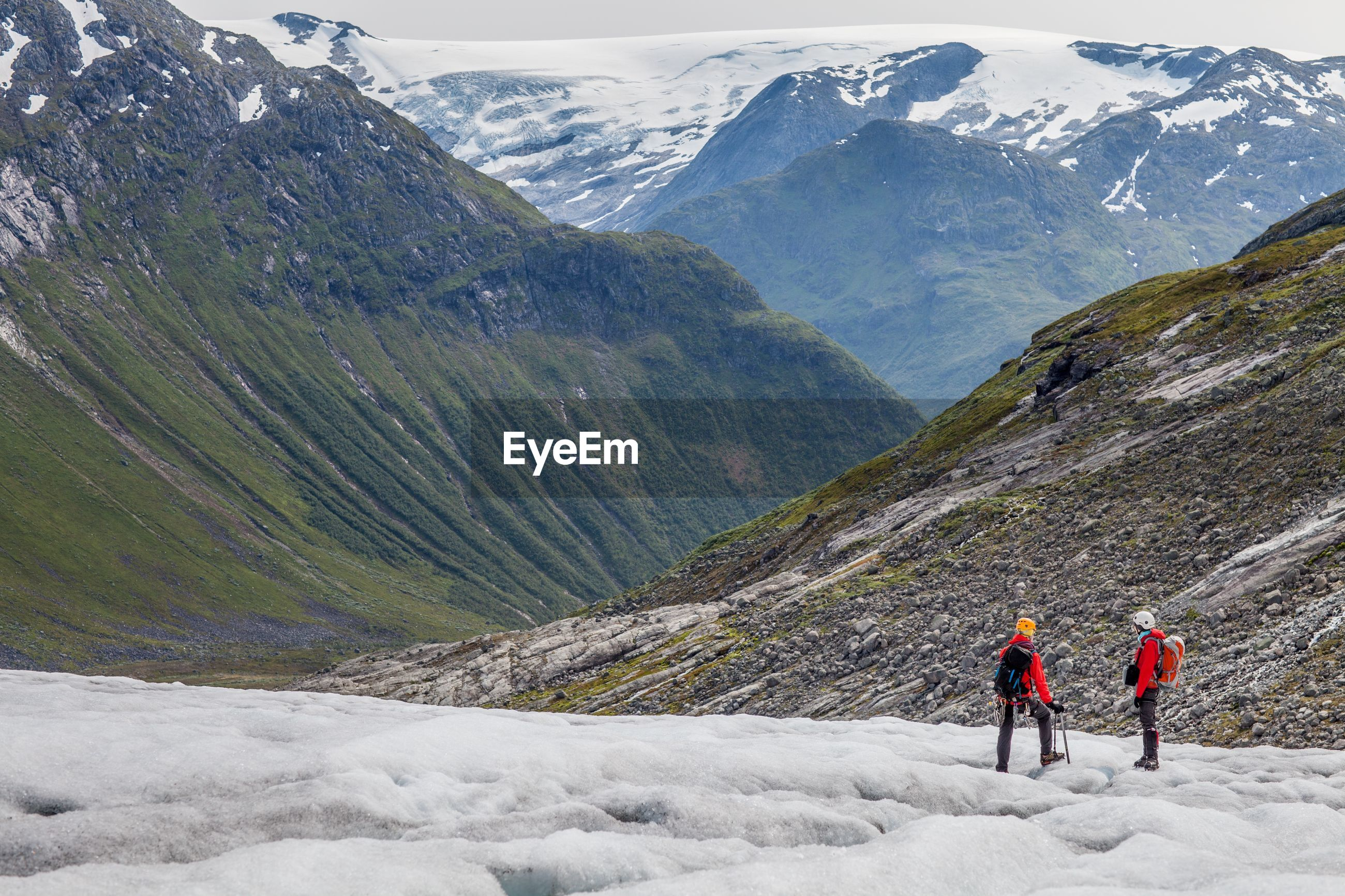 Rear view of hikers on glacier against rocky mountains