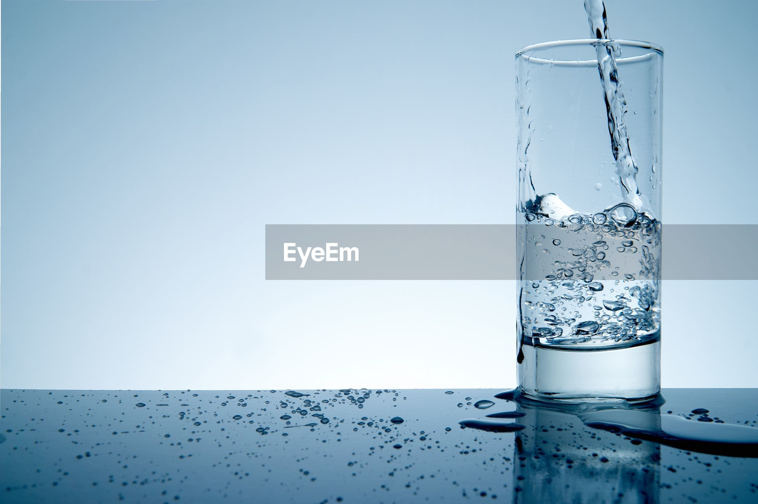 Water pouring in glass on table against white background