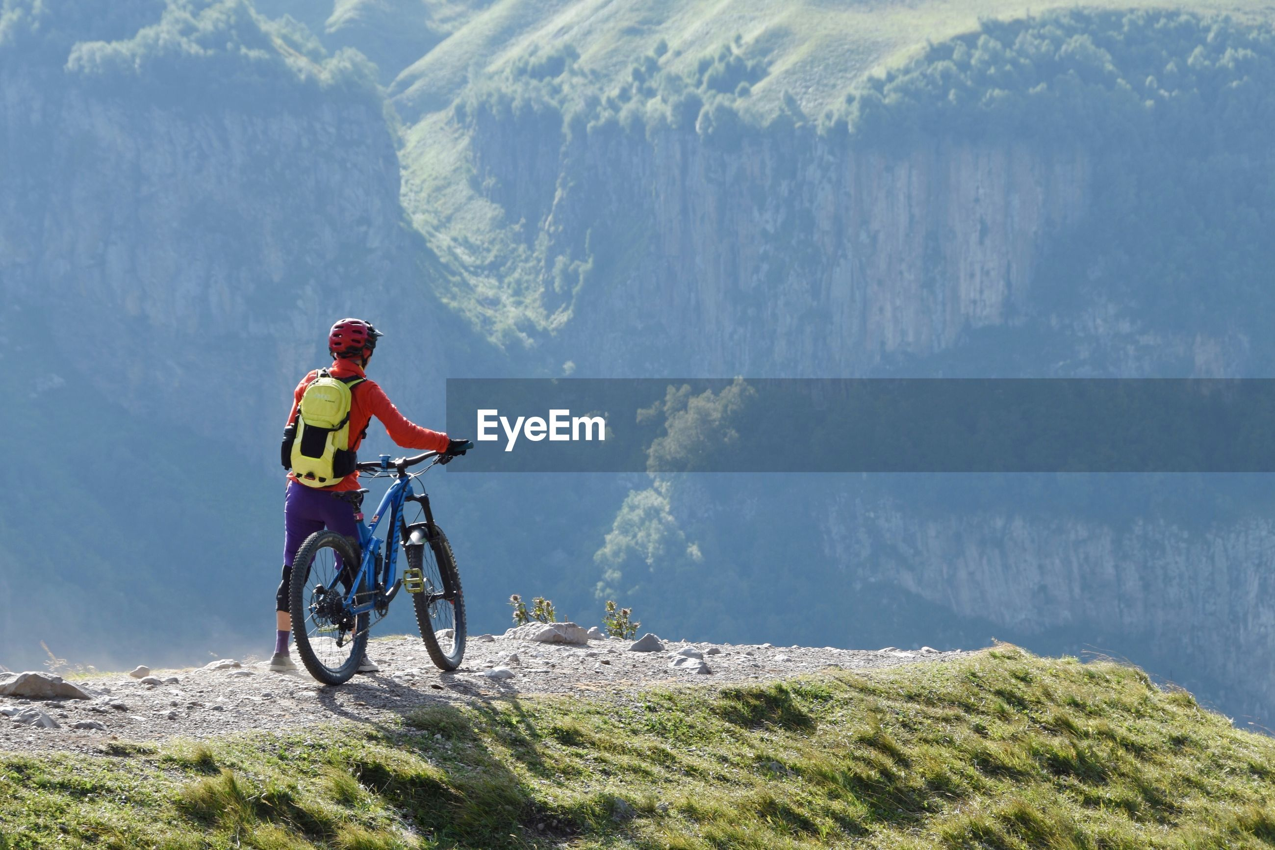 Rear view of man with bicycle standing on mountain peak