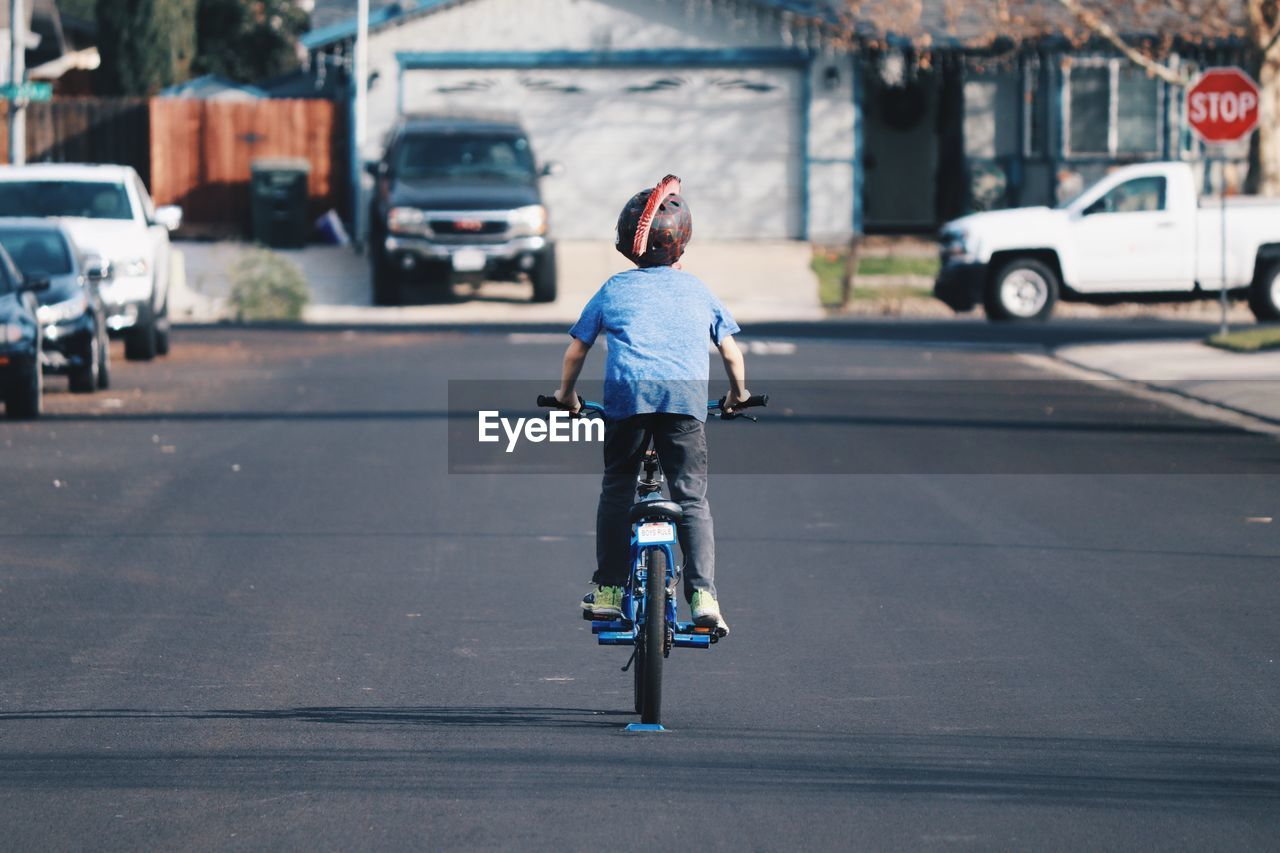 REAR VIEW OF GIRL RIDING BICYCLE ON STREET
