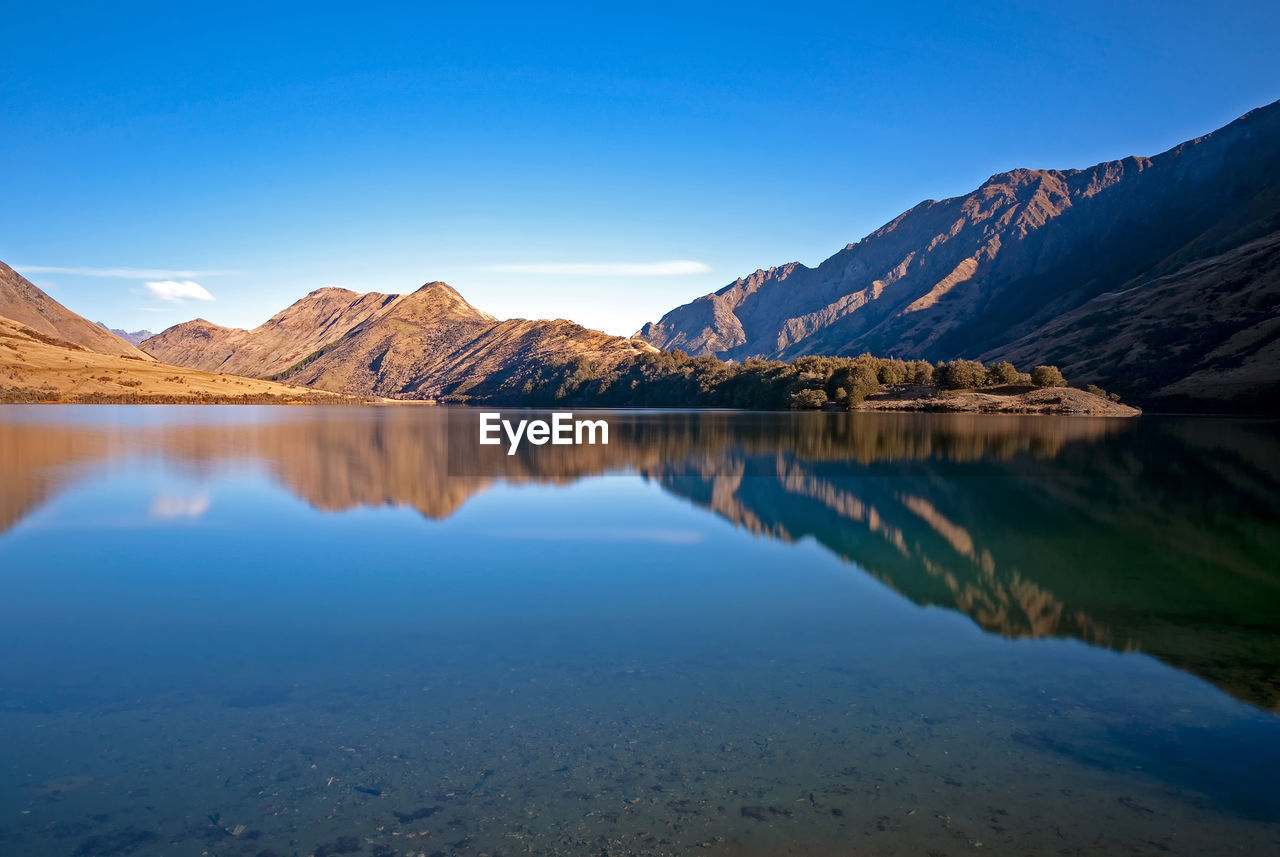 Scenic View Of Lake And Mountains Against Blue Sky