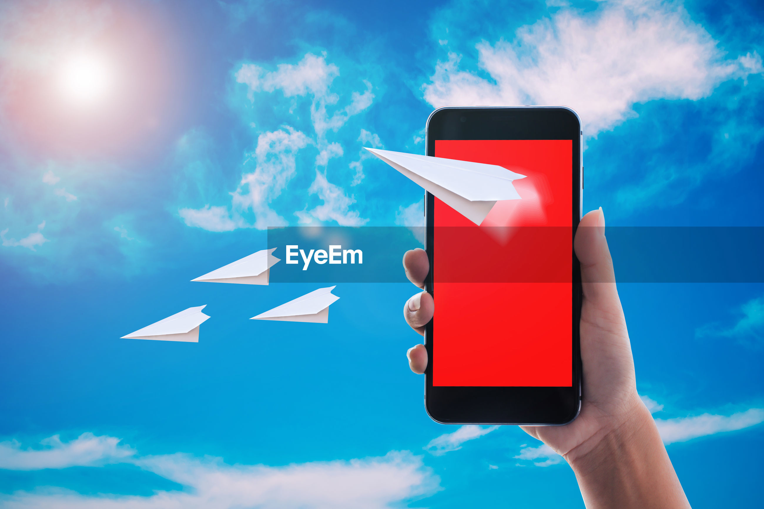Digital composite image of person holding smart phone with paper airplane against blue sky
