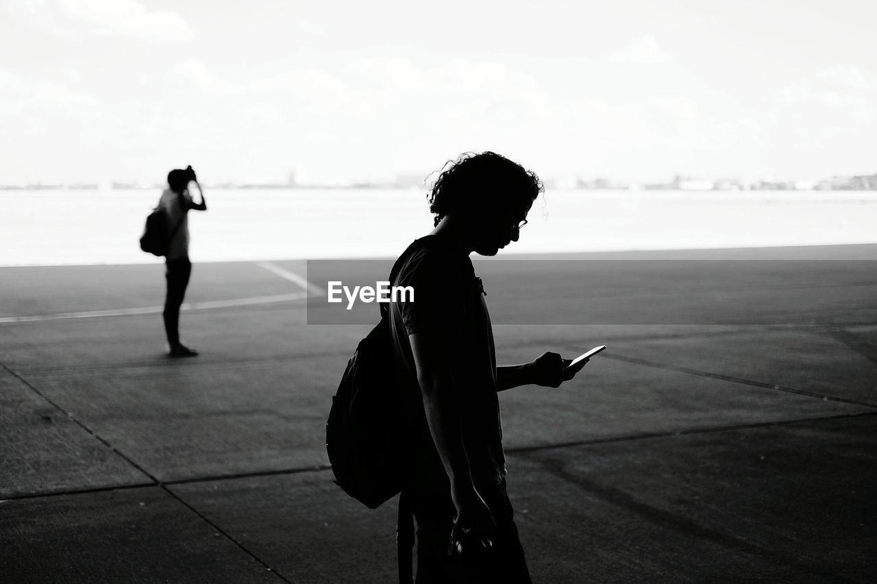 Side View Of Man Using Mobile Phone At Tempelhof Airport