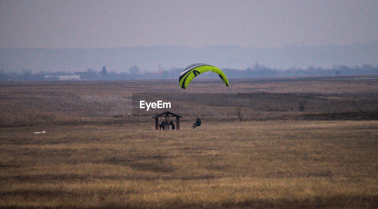 sky, adventure, landscape, environment, parachute, extreme sports, sport, land, field, nature, paragliding, leisure activity, freedom, mid-air, grass, transportation, day, outdoors, flying