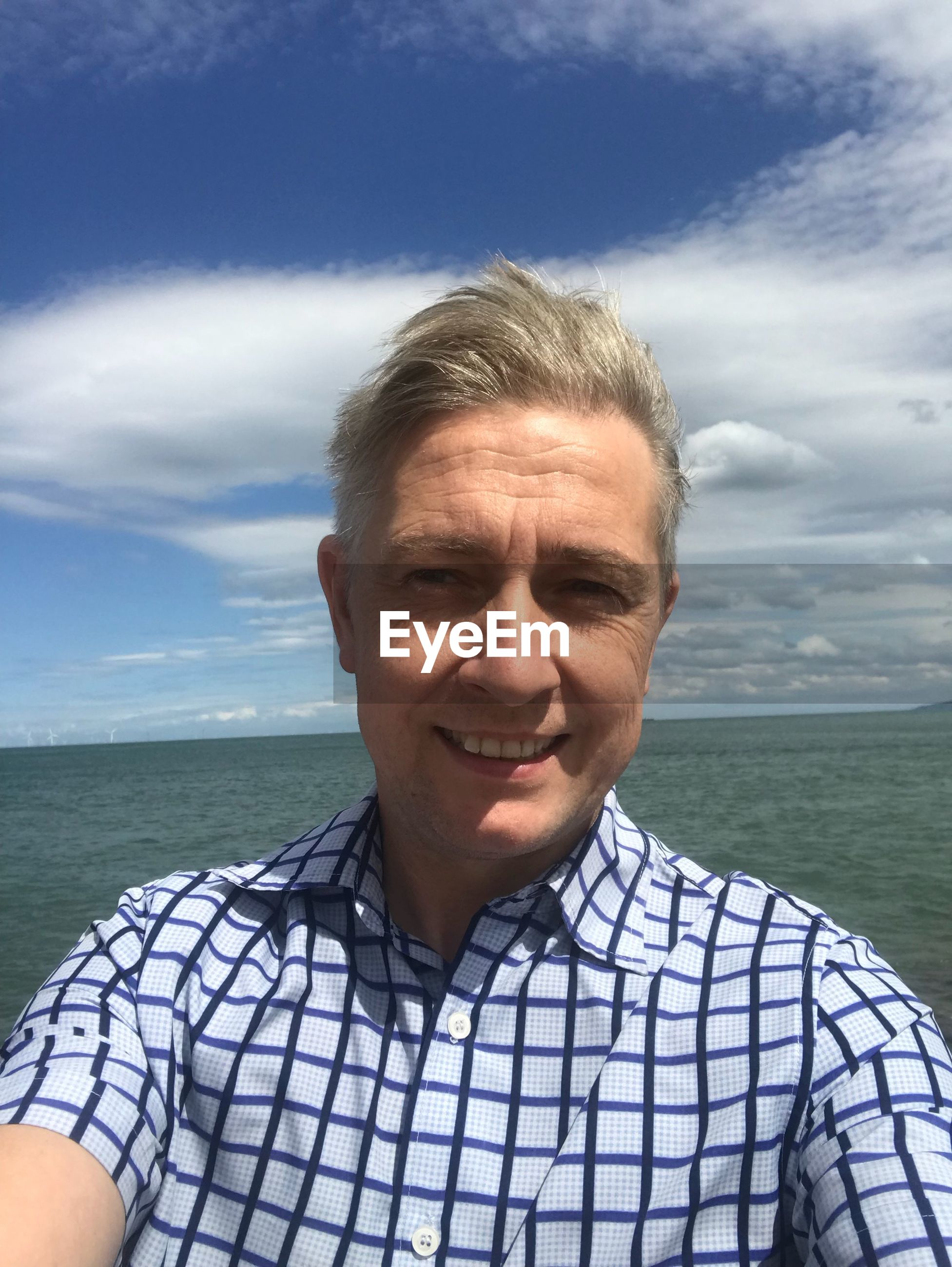 portrait, sea, front view, water, headshot, one person, sky, looking at camera, smiling, real people, cloud - sky, men, males, lifestyles, casual clothing, beauty in nature, leisure activity, mature adult, mature men, horizon over water, outdoors