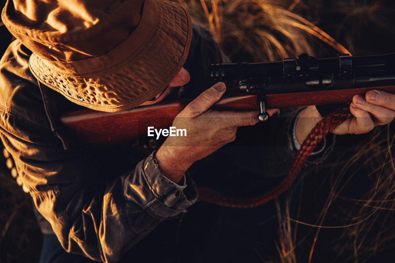 High Angle View Of Man Aiming Rifle