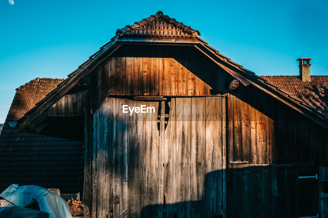 built structure, architecture, building exterior, wood - material, building, sky, house, nature, old, day, no people, sunlight, clear sky, blue, roof, outdoors, residential district, low angle view, barn, agricultural building