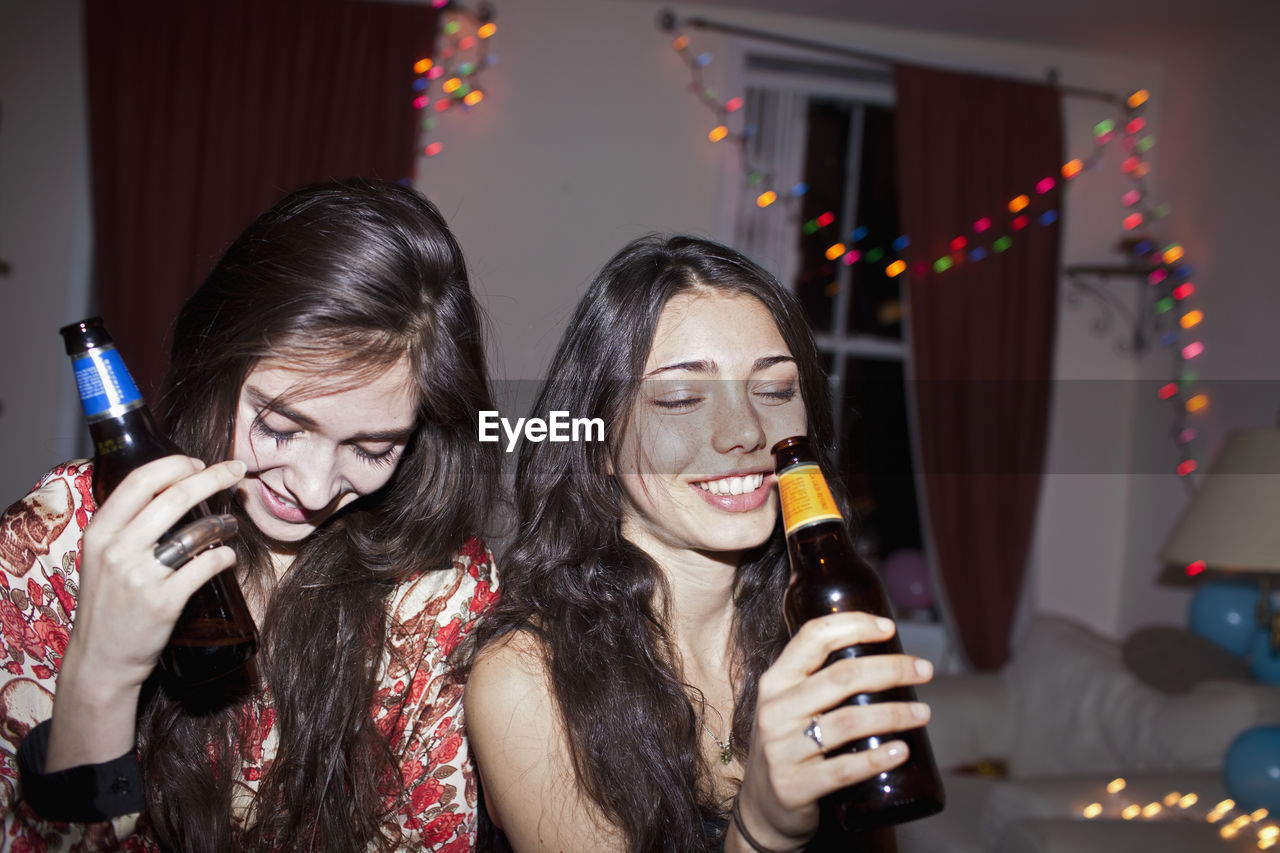 young adult, friendship, young women, happiness, celebration, leisure activity, event, lifestyles, togetherness, indoors, real people, adult, women, food and drink, enjoyment, party - social event, smiling, emotion, headshot, nightlife, hairstyle, wireless technology, hair, glass