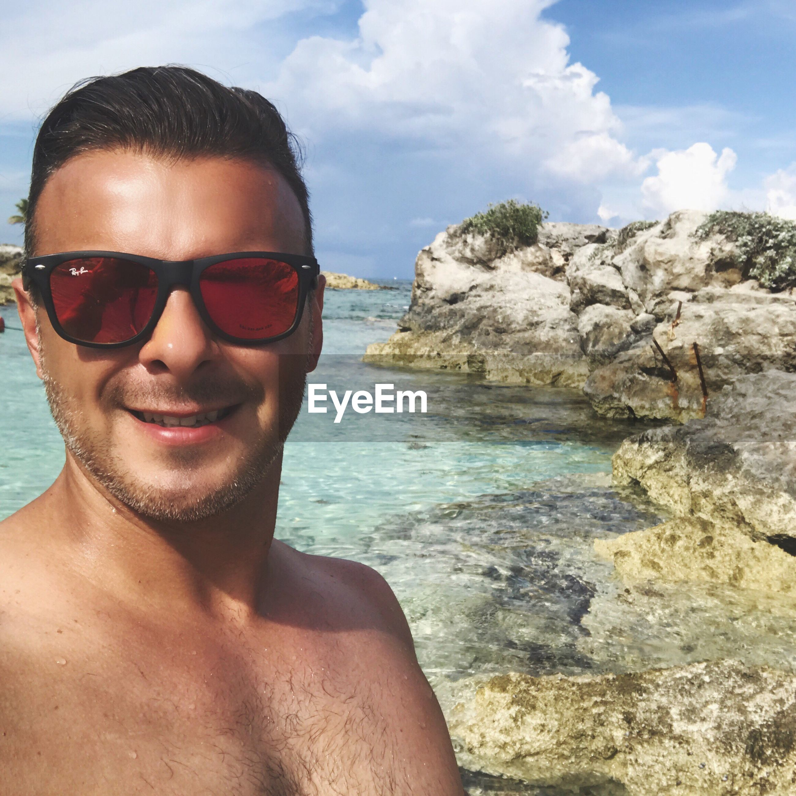 Close-up portrait of shirtless man wearing sunglasses on shore