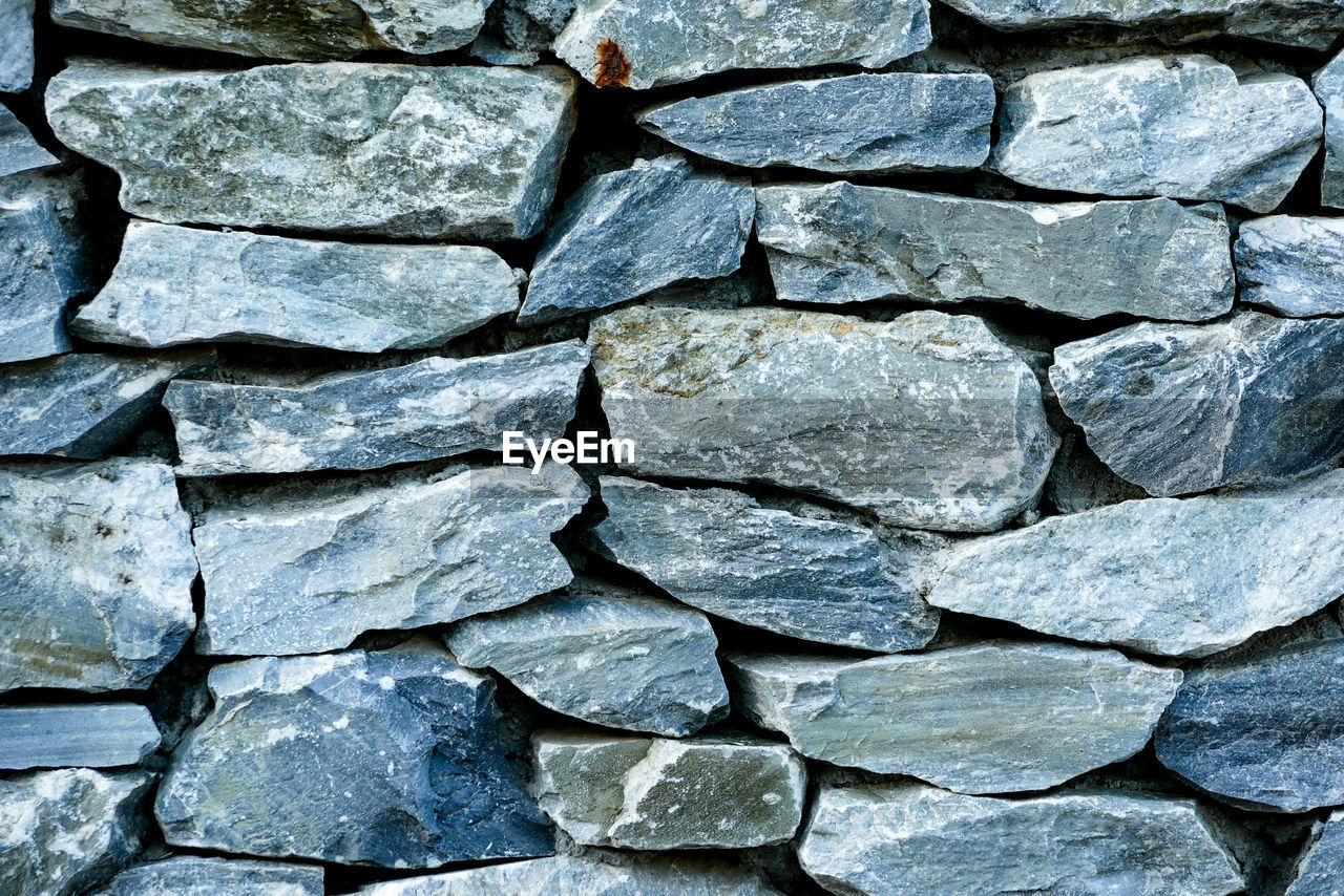 full frame, backgrounds, large group of objects, solid, stone - object, no people, abundance, textured, rough, rock, close-up, stone wall, pattern, day, nature, toughness, rock - object, gray, high angle view, outdoors, pebble